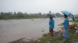 Warga melihat arus sungai di dekat gunung berapi Mayon di kota Daraga, provinsi Albay, selatan Manila (27/1). Pihak berwenang telah memperingatkan warga untuk menghindari sungai yang dapat mengancam masyarakat sekitar. (AFP Photo/Ted Aljibe)