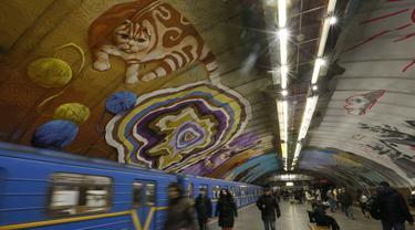 Penumpang melewati kereta di bawah mural yang menghiasi dinding stasiun metro bawah tanah kota di Kyiv, Ukraina, Rabu, (29/1/2020). (AP Photo / Efrem Lukatsky)