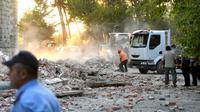 Petugas membersihkan puing-puing atap gedung yang runtuh sai gempa berkekuatan 5,6 magnitudo mengguncang Tirana, Albania (21/9/2019). Menurut lembaga survei Amerika Serikat, titik pusat gempa berada dekat Durres, kurang dari 40 kilometer sebelah barat ibu kota Tirana. (AFP Photo/Gent Shkullaku)