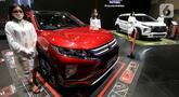Sales promotion girl (SPG) berpose di samping Mitsubishi Eclipse Cross yang dipamerkan pada ajang Indonesia International Motor Show (IIMS) Hybrid 2021 di JIExpo Kemayoran, Jakarta, Kamis (15/04/2021). (Liputan6.com/Pool/Mitsubishi)
