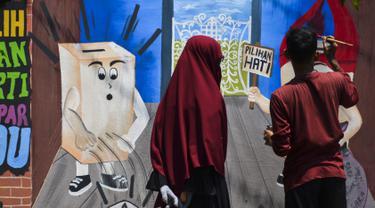 Seorang seniman menyelesaikan lukisan mural Pemilu 2019 di Banda Aceh, provinsi Aceh (17/3). Indonesia akan mengadakan pemilihan presiden dan parlemen secara serentak pada 17 April. (AFP Photo/Chaideer Mahyuddin)