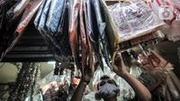 Abdullah merapikan kantong ramah lingkungan yang juga dijual di Pasar Tebet Barat, Jakarta, Selasa (30/6/2020). Meski dirinya juga telah menjual kantong ramah lingkungan, namun minat beli masyarakat tetap masih rendah. (merdeka.com/Iqbal S Nugroho)