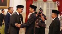 Presiden Joko Widodo didampingi Wapres Jusuf Kalla memberikan ucapan selamat kepada Agus Gumiwang Kartasasmita usai dilantik sebagai Menteri Sosial di Istana Negara, Jakarta, Jumat (24/8).(Liputan6/Pool/Gar)