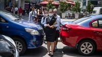 Pejalan kaki mengenakan masker di tengah kekhawatiran akan penyebaran virus corona COVID-19, di Kuala Lumpur, Malaysia, Kamis, (13/2/2020). Di Malaysia, ada 18 kasus virus Covid-19, sebanyak 12 kasus terjadi pada warga negara China, sedang enam lainnya warga lokal. (AFP/Mohd Rasfan)