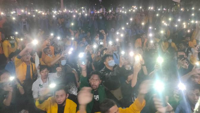 Para mahasiswa kompak menghidupkan lampu ponselnya, saat menggelar unjuk rasa di depan kantor Gubernur Sumsel di Palembang (Liputan6.com / Nefri Inge)