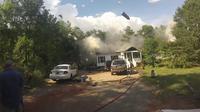 Sebuah kaleng aerosol terlihat terlempar dari dalam rumah dan terbang melejit hingga mengenai salah satu truk pemadam kebakaran.
