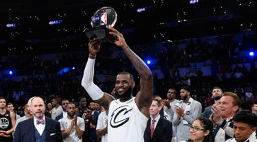 Pemain tim LeBron James, LeBron James mengangkat tropi usai timnya mengalahkan tim Stephen dalam pertandingan basket NBA All Star di Los Angeles, Amerika Serikat, Minggu (18/2). Tim LeBron menang dengan skor 148-145. (AP Photo/Chris Pizzello)
