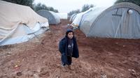 Seorang bocah laki-laki berdiri di jalanan berlumpur di kamp pengungsi Bab Al-Salam, dekat perbatasan Suriah-Turki, Provinsi Aleppo Utara, Senin (26/12). Di sini tercatat sekitar ribuan warga yang telah lama hidup di tenda. (REUTERS/Khalil Ashawi)