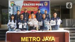 Petugas menunjukkan barang bukti beserta tersangka kasus dugaan penyiraman air keras kepada sembilan wanita di tiga lokasi berbeda di Polda Metro Jaya, Jakarta, Sabtu (16/11/2019). Polisi menangkap seorang tersangka dalam kasus ini. (Liputan6.com/Immanuel Antonius)