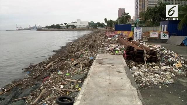 Pembersih dan sukarelawan menyapu tumpukan sampah yang ditinggalkan oleh Topan Mangkhut di sepanjang Teluk Manila, Minggu (16/9).