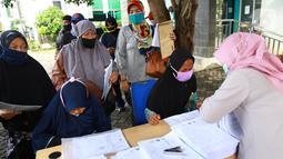 Warga antre menerima Bantuan Sosial Tunai (BST) di Kelurahan Pondok Benda, Kecamatan Pamulang, Tangerang Selatan, Minggu (10/01/2021). BST senilai Rp300 ribu akan disalurkan selama empat bulan berturut-turut mulai dari Januari - April 2021. (Liputan6.com/Fery Pradolo)