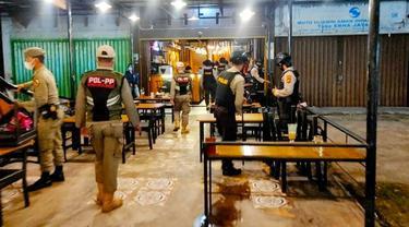 Personel Polresta Pekanbaru bersama Satpol PP membubarkan pengunjung cafe.