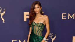 Aktris Zendaya berpose saat menghadiri Primetime Emmy Awards ke-71 di Microsoft Theater di Los Angeles (22/9/2019). Zendaya tampil dengan rambut ikal berwarna merah yang digerai ditambah sentuhan anting berlian yang semakin membuatnya tampak begitu glamor. (AFP Photo/Matt Winkelmeyer)
