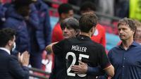 Pelatih Jerman, Joachim Loew, dan Thomas Muller berpelukan setelah kekalahan dari Inggris pada 16 besar Euro 2020 di Stadion Wembley, Selasa (30/6/2021). (Frank Augstein/AFP)