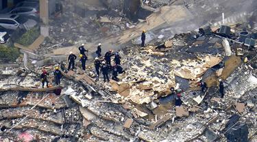 Petugas penyelamat melakukan pencarian di puing-puing Champlain Towers South Condo, Surfside, Miami, Florida, Amerika Serikat, Jumat (25/6/2021). Jumlah korban yang dinyatakan hilang dalam runtuhnya gedung apatemen 12 lantai tersebut telah meningkat menjadi 159 orang. (AP Photo/Gerald Herbert)