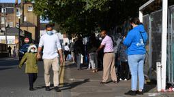 Orang-orang, beberapa memakai masker, mengantre untuk memasuki pusat pengujian virus corona di Edmonton, utara London, Kamis (17/9/2020). PM Inggris Boris Johnson mengatakan dirinya bisa menutup pub-pub lebih awal sebagai pencegahan kenaikan kasus Covid-19 untuk kedua kalinya. (JUSTIN TALLIS/AFP)
