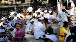 Suasana khusyuk saat umat Hindu tengah berdoa selama perayaan Kuningan di sebuah pura di Pulau Serangan, Denpasar, Bali, Sabtu (20/2). Kuningan merupakan hari terakhir dari perayaan Galungan. (AFP PHOTO/SONNY Tumbelaka)