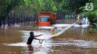 Warga menjala ikan di tengah jalan yang tertutup banjir di kawasan TB Simatupang, Jakarta Selatan, Sabtu (20/2/2021). Banjir terjadi akibat luapan Kali Serua yang berada di pinggir jalan tol. (merdeka.com/Arie Basuki)