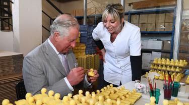 Pangeran Charles melukis sabun wangi  berbentuk bebek selama kunjungannya ke pabrik laboratorium Parfumerie Fragonard di Eze, dekat Nice, Prancis selatan, (7/5). (AFP Photo/Pool/Boris Horvat)