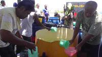 Polda Gorontalo mendistribusikan ari bersih kepada warga di beberapa kecamatan di Gorontalo. Pemerintah Provinsi Gorontalo menetapkan status darurat kekeringan seiring dengan musim kemarau panjang. (Liputan6.com/ Andri Arnold)