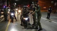 Polisi memeriksa pengendara sepeda motor saat jam malam untuk mencegah penyebaran COVID-19 di Metro Manila, Filipina, Senin (15/3/2021). Kementerian Kesehatan Filipina melaporkan lonjakan kasus COVID-19 selama lebih dari seminggu. (AP Photo/Aaron Favila)