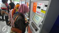 Calon penumpang membeli tiket di mesin penjual tiket kereta api otomatis di Stasiun Senen, Jakarta, Selasa (20/12). Jelang libur Natal dan tahun baru tiket Kereta Api sudah habis untuk keberangkatan Jateng dan Jatim. (Liputan6.com/Angga Yuniar)