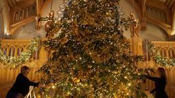 Dekorator menghias pohon cemara besar dari Windsor Great Park di ujung aula St. George di Windsor Castle, Inggris, 30 November 2018. Pohon setinggi 6 meter itu dihias dengan pernak-pernik Natal berwarna emas serta ornamen kerajaan.  (AP/Frank Augstein)
