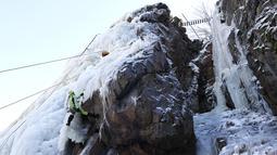 Aksi seorang perempuan memanjat dinding es buatan di desa Vir, Republik Ceko, Minggu (14/2/2021). Ketika suhu turun di Republik Ceko, pemanjat tebing memanfaatkan kondisi beku dengan mengubah permukaan batu menjadi dinding es setinggi 20 meter untuk pendaki. (AP Photo/Petr David Josek)