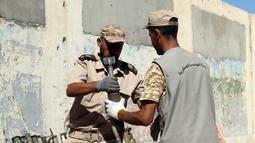 Pasukan pemerintah Libya yang didukung PBB memindahkan sisa-sisa bahan peledak di sebuah kamp militer di Tripoli selatan, Libya (22/7/2020). (Xinhua/Hamza Turkia)