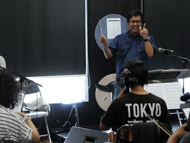 Musisi legendaris, Iwan Fals menjalani sesi latihan bersama Erwin Gutawa Orchestra, Jakarta, Minggu (21/8). Iwan Fals menuturkan akan menampilkan sajian yang spektakuler di HUT SCTV ke-26 dengan iringan musik orkestra. (Liputan6.com/Helmi Afandi)