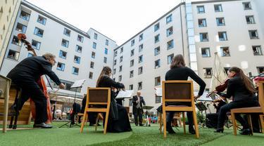 """Para tamu Zeitgeist Hotel menikmati dari kamar mereka penampilan penyanyi Monika Medek dan Dagmar Dekanovsky serta orkestra Camerata Carnutum di Wina, Sabtu (30/5/2020). """"Konser jendela"""" diadakan untuk merayakan pembukaan kembali hotel di Austria di tengah pandemi COVID-19. (JOE KLAMAR/AFP)"""