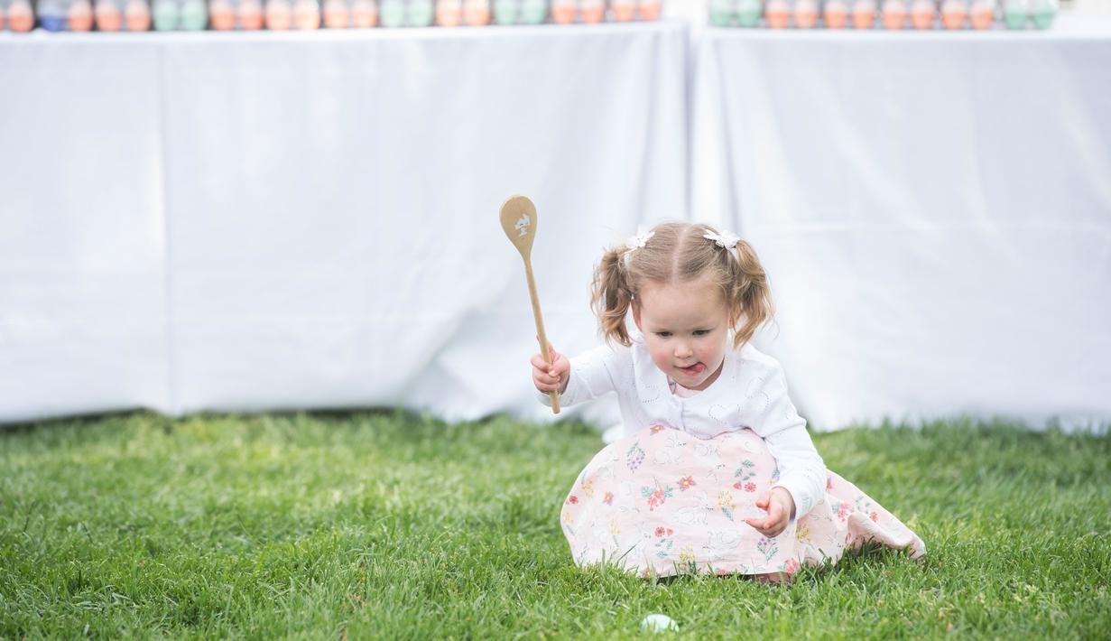 Seorang bocah mengikuti lomba menggelindingkan telur paskah ke-141 di halaman Gedung Putih, Washington, Senin (22/4). Acara tahunan tersebut merupakan bagian dari rangkaian memperingati Paskah yang rutin diselenggarakan di South Lawn Gedung Putih. (Kevin Wolf/AP Images for the American Egg Board)