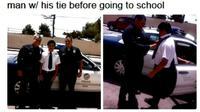 Seorang polisi yang berdinas menyempatkan diri menolong seorang pelajar yang kesulitan memasang dasi.