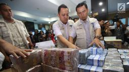 Petugas menata barang bukti hasil tindak pidana pencucian uang (TPPU) kasus narkoba di kantor BNN, Jakarta, Selasa (13/6). Total senilai Rp 39 miliar disita dari empat tersangka yang terkait dengan jaringan Freddy Budiman. (Liputan6.com/Yoppy Renato)