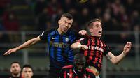 Duel udara yang dilakukan Ivan Perisic dan Andrea Conti pada laga lanjutan Serie A yang berlangsung di Stadion San Siro, Milan, Senin (18/3). Inter Milan menang 3-2 atas AC Milan. (AFP/Miguel Medina)
