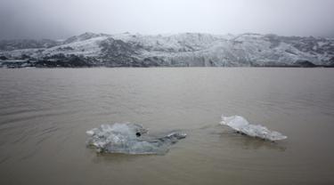 Foto yang diambil 16 Oktober 2015 menunjukkan bongkahan es terapung di perairan Gletser Solheimajokull, Islandia. Pemanasan global menyebabkan gletser Solheimajokull mencair hingga 1 km sejak pengukuran tahunan pada 1931. (AFP PHOTO/POOL/Thibault Camus)