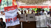 Petugas KPPS memperlihatkan contoh surat suara kepada pemilih saat simulasi pemungutan dan pencoblosan surat suara Pemilu 2019 di Taman Suropati, Jakarta, Rabu (10/4). Simulasi itu untuk meminimalisir kesalahan dan kekurangan saat pencoblosan pemilu pada 17 April nanti. (Liputan6.com/Johan Tallo)