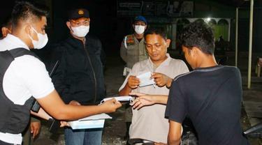 Kapolresta Pekanbaru Kombes Nandang memberikan masker kepada warga yang tidak taat protokol kesehatan.