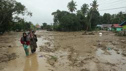 Penduduk desa berjalan melalui daerah banjir di desa Radda di Kabupaten Luwu Utara, Sulawesi Selatan (14/7/2020). Akibat musibah banjir bandang ini setidaknya sekitar 15 orang tewas dan belasan lainnya dinyatakan hilang. (AFP/Aryanto)