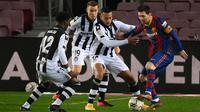 Striker Barcelona, Lionel Messi, berusaha melewati pemain Levante pada laga Liga Spanyol di Stadion Camp Nou, Senin (14/12/2020). Barcelona menang dengan skor 1-0. (AFP/Lluis Gene)