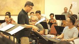 Konduktor Avip Priatna memimpin latihan Jakarta Concert Orchestra (JCO) di Balai Resital Kertanegara, Jakarta, Rabu (28/11). Konser Beat It-A Tribute To Michael Jackson akan dilangsungkan pada 1 Desember 2018. (Fimela.com/Bambang Purnama)