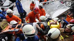 Petugas gabungan saat mengevakuasi salah satu korban rumah roboh di Jalan Pulo, Tanah Tinggi, Johar Baru, Jakarta Pusa, Jumat (26/4). Akibat kejadian tersebut mengakibatkan enam orang masih terjebak Korban selamat 4 orang dan yang meninggal 2 orang. (Liputan6.com/Herman Zakharia)