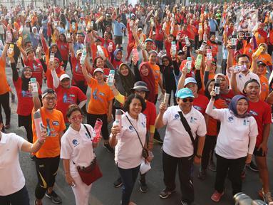 Warga mengangkat tumbler saat mengikuti gerakan 1 juta  tumbler di GBK, Senayan, Jakarta, Minggu (28/7/2019). Gerakan 1 juta  tumbler dicanangkan untuk indonesia tanpa plastik. (Liputan6.com/Angga Yuniar)