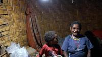 Seorang ibu dan anaknya duduk di bawah Lampu Tenaga Surya Hemat Energi (LTSHE) di Distrik Puldama, Kabupaten Yahukimo, Provinsi Papua. LTSHE bisa dinyalakan secara manual lewat tombol di lampu atau dengan remote control. (Liputan6.com/HO/Hadi M Juraid)
