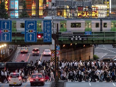 Pejalan kaki menyeberangi jalan raya saat kereta Yamanote Line melintas pada jam sibuk di Distrik Shinjuku, Tokyo, Jepang, Selasa (4/6/2019). Yamanote loop line menawarkan wisatawan untuk melihat kehidupan sehari-hari warga di pusat Kota Tokyo. (AP Photo/Jae C. Hong)