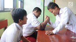 Arya Permana sedang bermain bersama temannya di dalam kelas di SDN Cipurwasari 1 kawasan Karawang, Jawa Barat, Selasa (9/4). Arya Permana diketahui memiliki berat badan hingga 192 kg, sekarang sudah turun 105 kg menjadi 87 kg pasca operasi lambung. (Liputan6.com/Herman Zakharia)