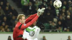 Pemain Wolfsburg, Dante berebut bola dengan kiper KAA Gent, Matz Sels pada leg kedua babak 16 besar  Liga Champion di di Volkswagen Arena, Wolfsburg, Rabu (9/3/2016) dini hari WIB. (AFP/Odd Andersen)