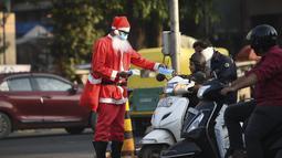 Aksi presiden Angel Foundation dan pekerja sosial, Rufas Christian, yang berpakaian Sinterklas memberikan masker kepada pengendara di persimpangan lalu lintas di Ahmedabad, India, Kamis (17/12/2020). India sejauh ini telah mencatat hampir 10 juta kasus Covid-19. (SAM PANTHAKY/AFP)