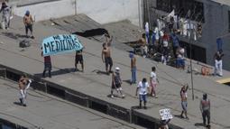 """Narapidana membawa poster yang bertuliskan """"Tidak ada obat-obatan"""" saat menggelar protes di Penjara Lurigancho, Lima, Peru, Selasa (28/4/2020). Narapidana mengeluhkan pihak berwenang tidak berbuat cukup untuk mencegah penyebaran COVID-19 dalam penjara. (AP Photo/Rodrigo Abd)"""