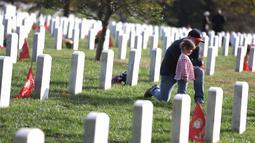 Kip Hogan didampingi putrinya mengunjungi makam temannya Army Gunnery Sgt. Terry Ball saat peringatan Hari Veteran, Arlington, Virginia, AS, Senin (11/11/2019). Rakyat AS memperingati Hari Veteran untuk menghormati mereka yang pernah bertugas di militer AS. (Alex Wong/Getty Images/AFP)